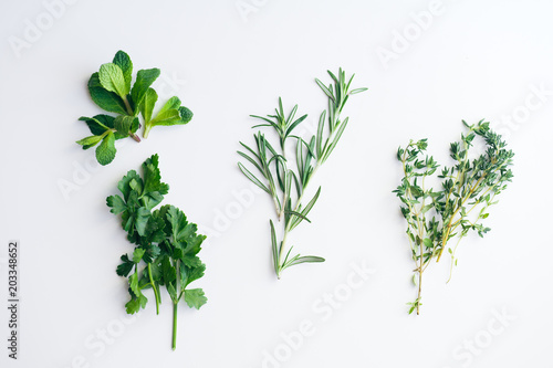 Fotografie, Obraz  Fresh herbs on white background: rosemary, thyme, mint and parsley in small bunc