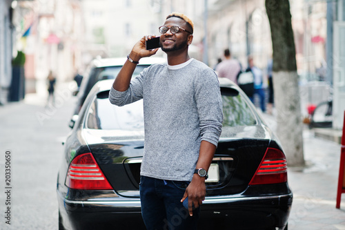 652af87d8ac Stylish african american boy on gray sweater and glasses posed at street  against black business car