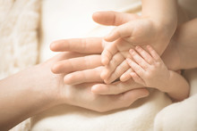 Newborn Child Hand. Closeup Of Baby Hand Into Parents Hands. Family, Maternity And Birth Concept.