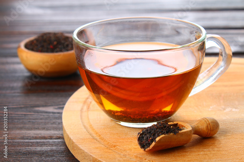 Poster Thee Hot black tea in a glass cup and dry tea on a wooden table.