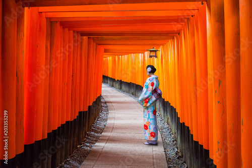 Poster Kyoto Woman in traditional kimono standing at the tunnel of torii gates, Japan