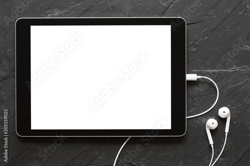 Tablet with empty screen and earphones on black stone surface