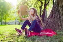 Girl Child In Glasses Reading Book In The Park