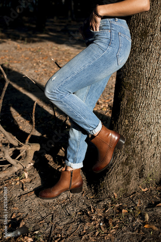 Photo  Brown shiny leather womens chelsea boots on woman legs with blue jeans in autumn forest or park