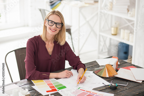 Color order. Pleasant female designer sitting at table while taking notes