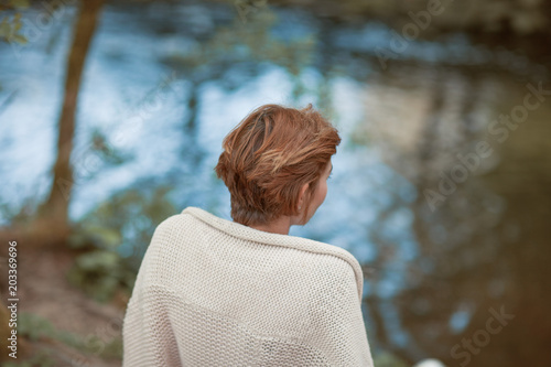 female traveller in casual clothes from behind, standing at a lake, enjoying nature, leisure concept