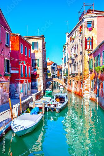 Side canal with moored motorboats in Venice