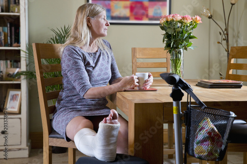 Mature Woman With Leg In Plaster Cast Sitting By Table At Home With Hot Drink