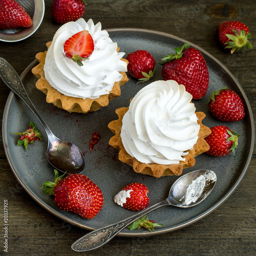 Sweet dessert. Round cakes with airy protein cream and fresh ripe strawberries on an old dish on a wooden table.