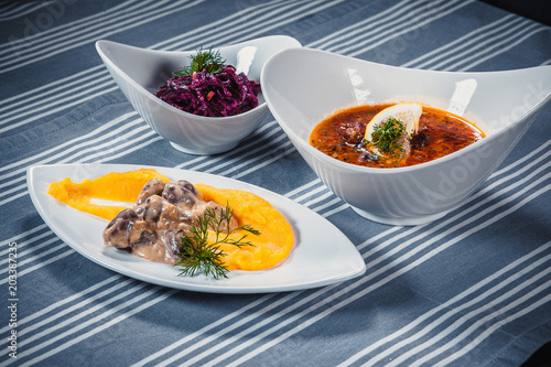 Deurstickers Klaar gerecht Set of three dishes. Business lunch of three dishes. Three dishes on white plates on a table with a blue tablecloth striped. Soup, salad and hot dish.