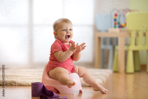 Photo Little baby toddler girl claps sitting on chamberpot in nursery room