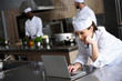 canvas print picture - attractive chef using laptop at restaurant kitchen