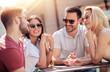 Happy friends talking in summer cafe