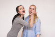 Portraits on the gray background of two girls girlfriends showing emotions.