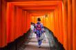 Leinwanddruck Bild - Woman in traditional kimono walking at torii gates, Japan