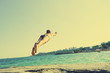 Sporty healthy man jumping into the sea during summer vacation, image with toning