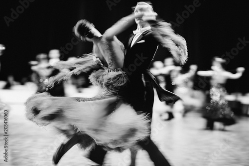couple dancers ballroom dancing blurred motion black-and-white image