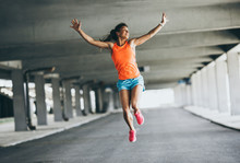 Young Female Runner Jumps On T...