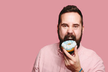 Sweet Tooth - Hungry Man Taking A Big Bite Of A Blue Donut, Isolated On Pink Studio Background