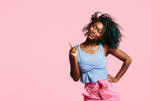 Cool Young Girl With Blue Tinted Hair Pointing And Looking Up, Isolated On Pink Studio Background