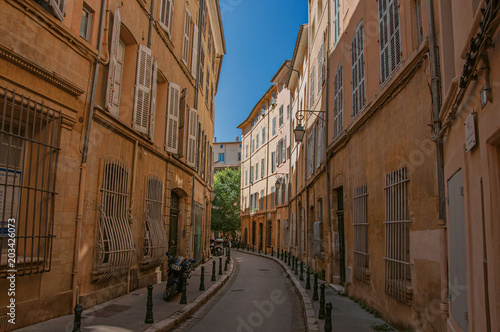 Narrow alley with tall buildings in the shadow in Aix-en-Provence, a pleasant and lively town in the French countryside Wallpaper Mural