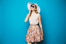 Beautiful And Fashionable Blonde Model Girl In Beige Blouse, Pink Skirt, Stylish Sunglasses And Hat Smiling And Posing In Studio At Blue Background