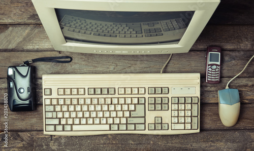 Retro stationary computer on a rustic wooden desk, vintage workspace. Monitor, keyboard, computer mouse, top view, flat lay.