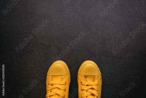 Obraz Stylish yellow sneakers on dark background - fototapety do salonu