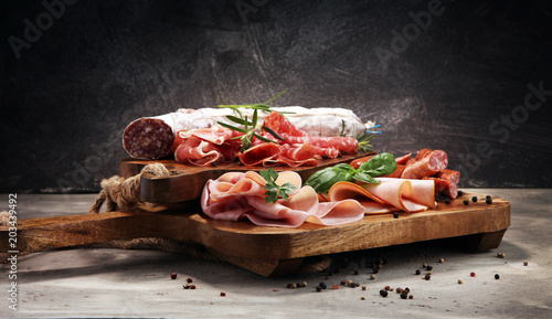 Food tray with delicious salami, ham,  fresh sausages and herbs. Meat platter with selection