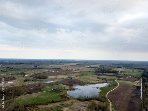Foto op Canvas Chocoladebruin drone image. aerial view of rural area with countryside lake enclosed by fields and forests