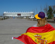 girl fan in a headdress in yellow purple color, goes to the stadium, carries on the shoulders of the flag of Spain