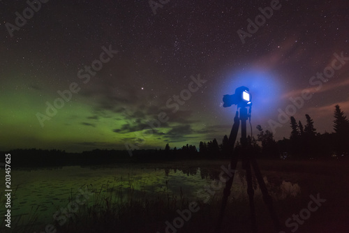 Photo  Aurora reflecting of a lake, city lights lighting up clouds - Camera in forgroun