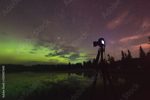 Aurora reflecting of a lake, city lights lighting up clouds - Camera in forgroun Poster