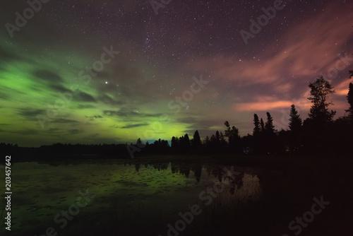 Fotografia, Obraz Aurora reflecting of a lake, city lights lighting up clouds