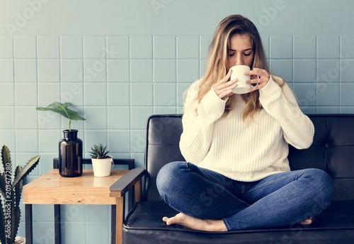 Papiers peints Voile A Caucasian Woman Sitting and Drinking Coffee