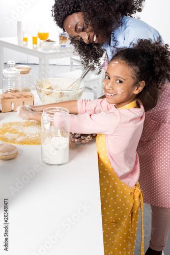 Foto op Plexiglas Bakkerij african american mother and smiling daughter kneading dough together on kitchen