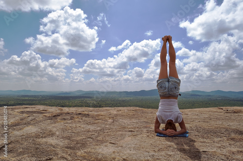Valokuvatapetti caucasian woman in yoga asana is standing on the top of the hill