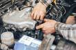 dirty hands of auto mechanic reparing car