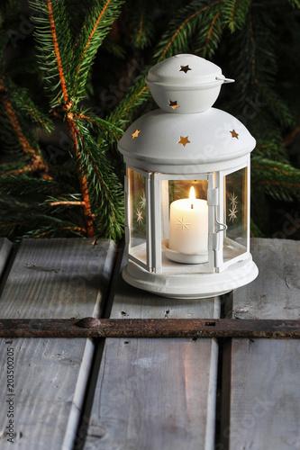 White lantern on wooden table under fir branch. Poster