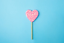 A Pink And White Spiral Heart Lollipop On Blue Background, Flat Lay Minimal Concept, Trendy Pop Art Style Photo, Isolated