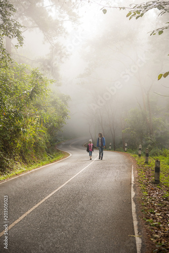 Fotografia, Obraz  A little girl and mother run on a road in the forest