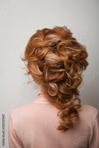 Hairstyle Greek braid on the head of a red hair woman back view close-up on a gray background.