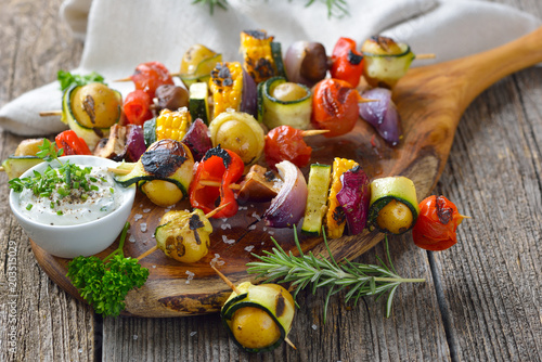 Vegan grillen: Bunte Gemüsespieße vom Grill mit Kräuterdip - Grilled skewers with mixed vegetables served on a wooden cutting board with a vegan herb dip