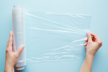 Woman's Hand Using A Roll Of Transparent Polyethylene Food Film For Packing Products On The Pastel Blue Table. Empty Place For Text Or Logo.