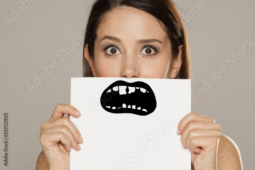 young woman with bad teeth drawn on paper on gray background Tablou Canvas