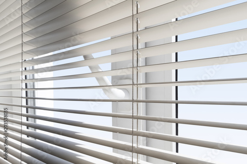 Photo White plastic window with blinds close-up against a blue sky.