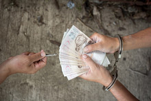 Hand Of A Man In Handcuffs Giving Bribe , Prisoner Give Money For Freedom