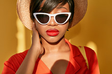 Sunny Portrait Of Young Black Woman With Big Red Lips And Short Brown Hair In Hat, White Sunglasses And Orange Red Dress. Yellow Background