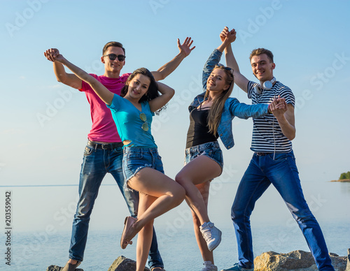 Fotografia  Friends are have fun and dancing along on a seashore, holding hands and laughing