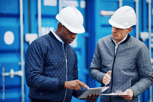 Two engineers discussing shipping logistics in a freight yard Canvas Print